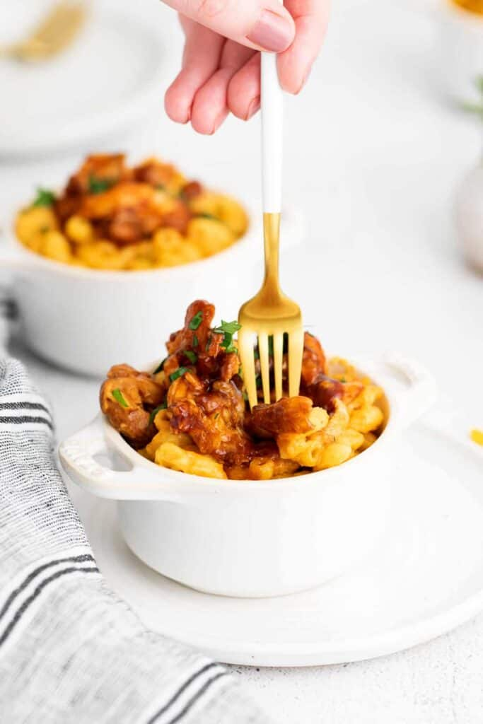 A fork taking a bite of bbq chicken.