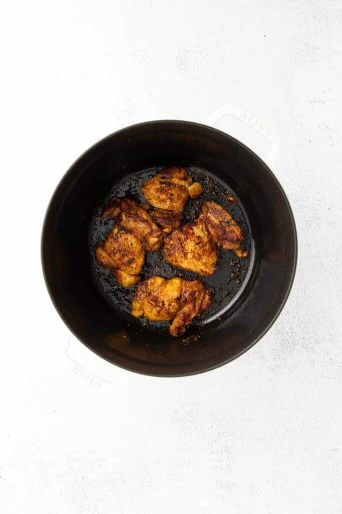 BBQ chicken thighs being cooked in a pot.