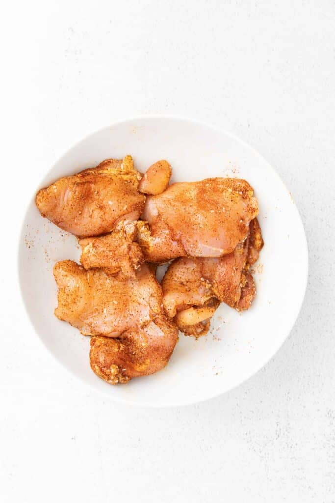 A plate of raw and seasoned boneless, skinless chicken thighs.