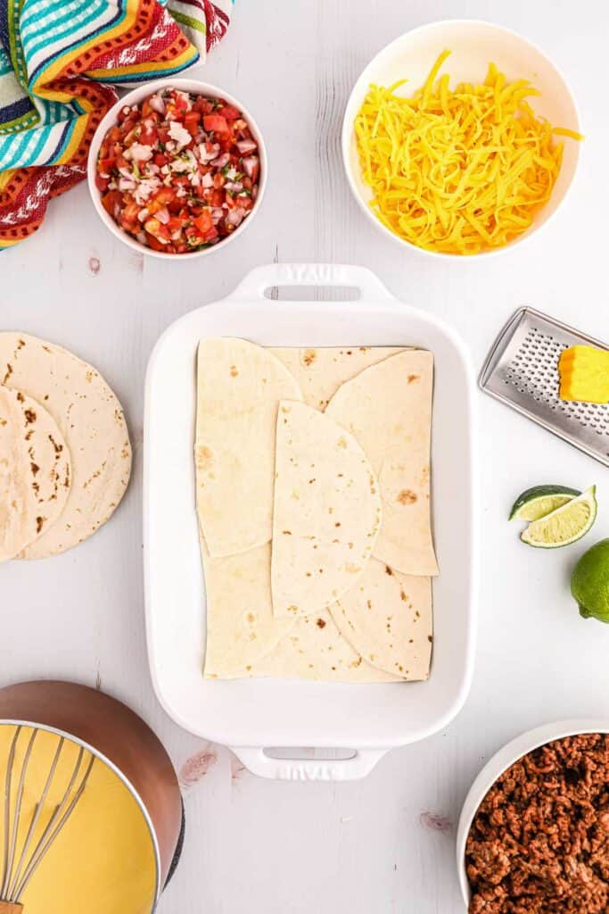 A casserole dish with tortillas laid out on the bottom.