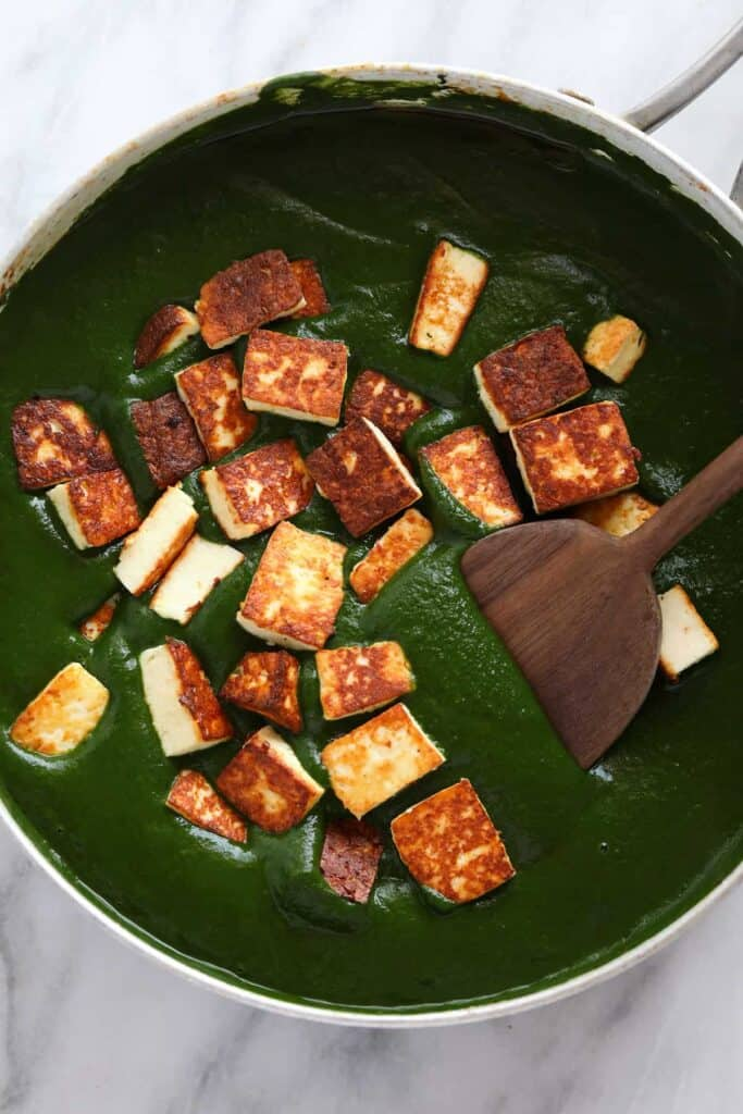 Paneer added to curry sauce.