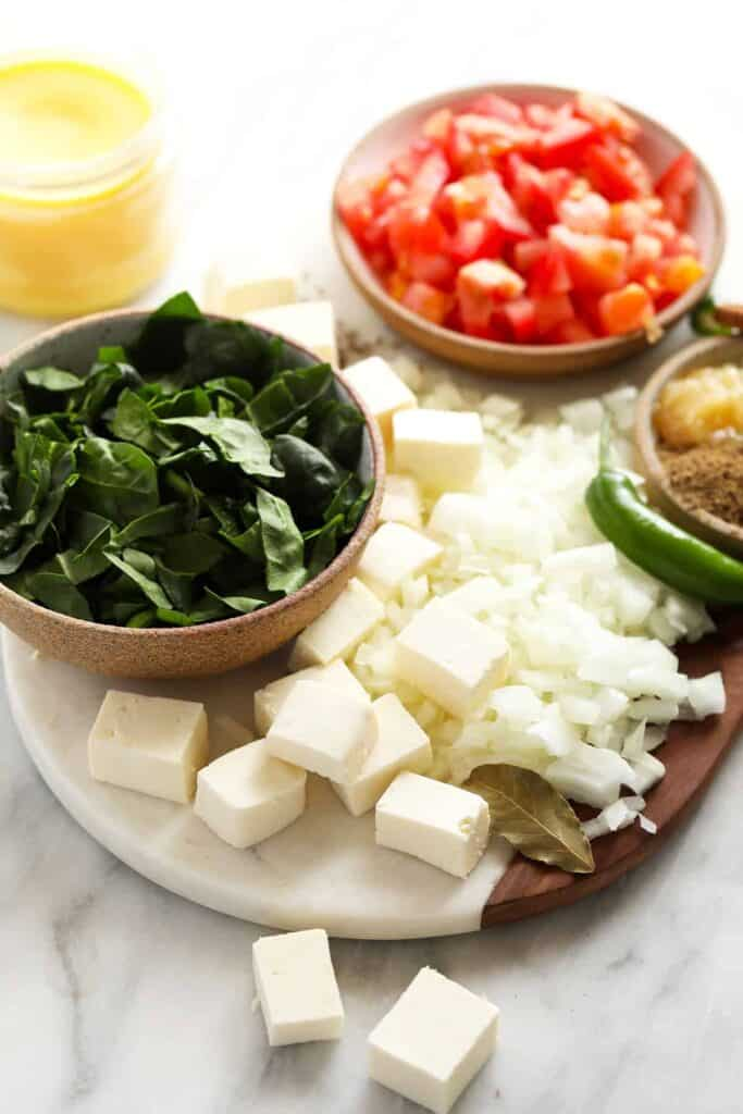 All the ingredients for palak paneer on a cutting board.