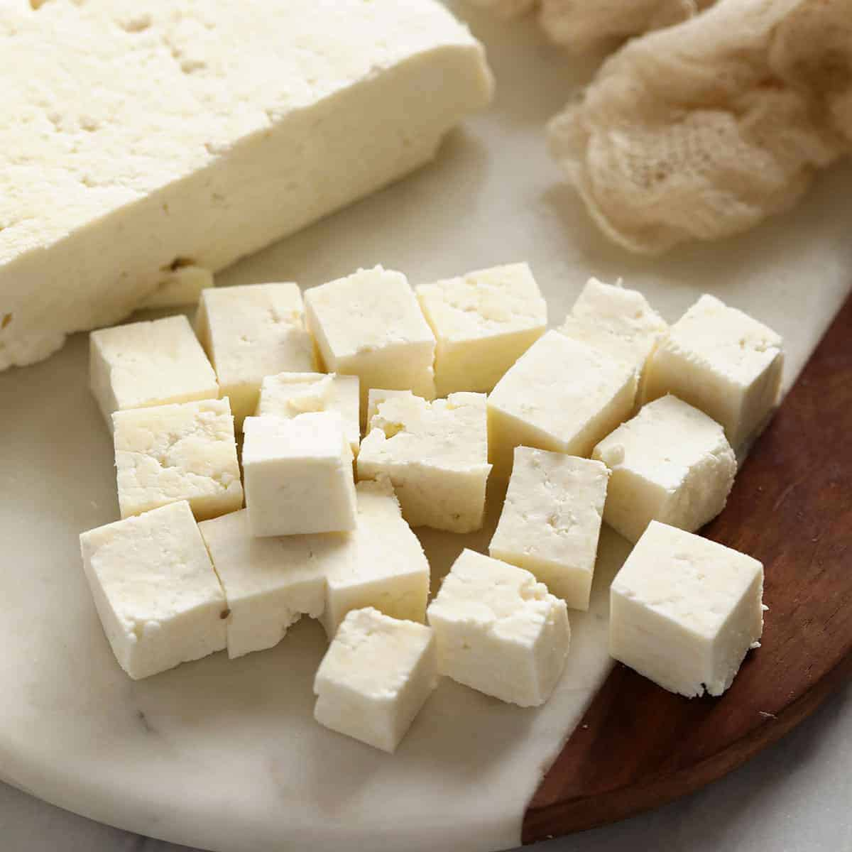 Paneer cut into cubes on cutting board