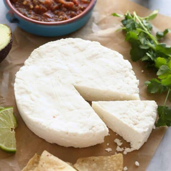queso fresco on parchment paper with chips and salsa.