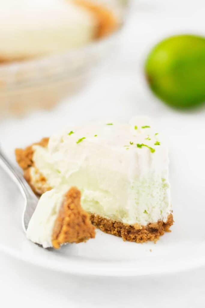 A fork taking a bite out of one pieces of key lime pie.