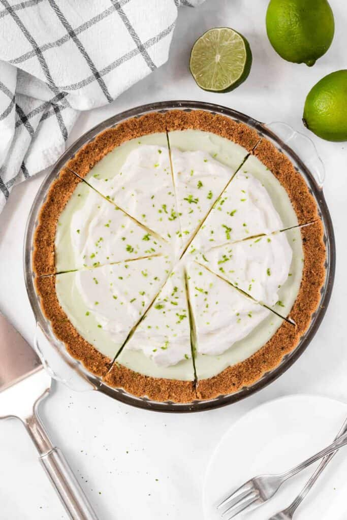 A key lime pie with cream cheese with fresh lime zest on top.