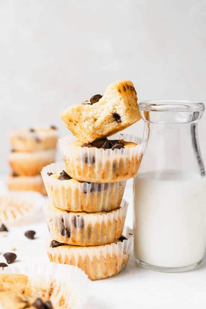 chocolate chip ricotta muffins in muffin liners next to a glass of milk