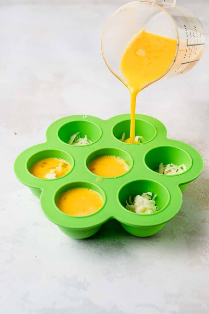 egg mixture being poured in silicone molds for instant pot cheesy egg bites