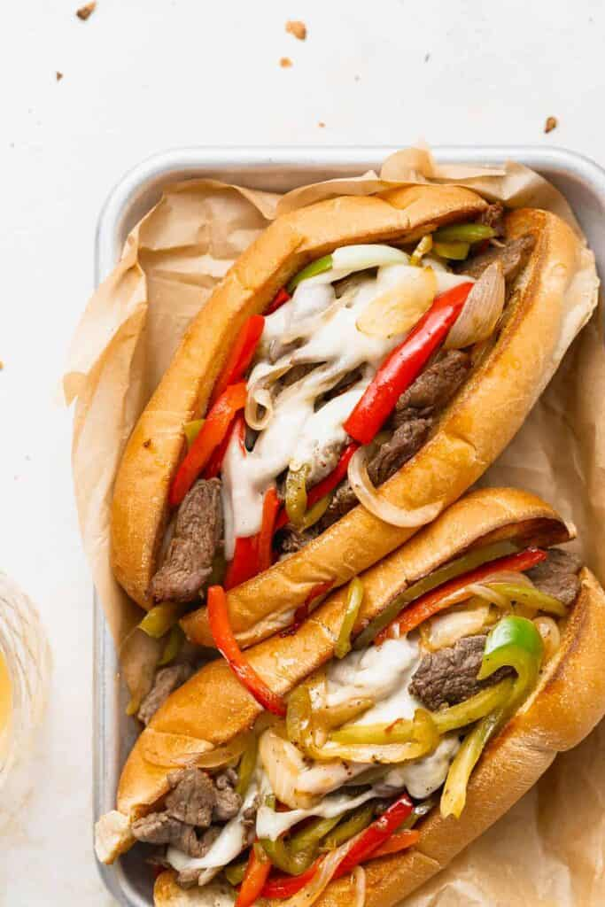 Two philly cheesesteak sandwiches on a plate.