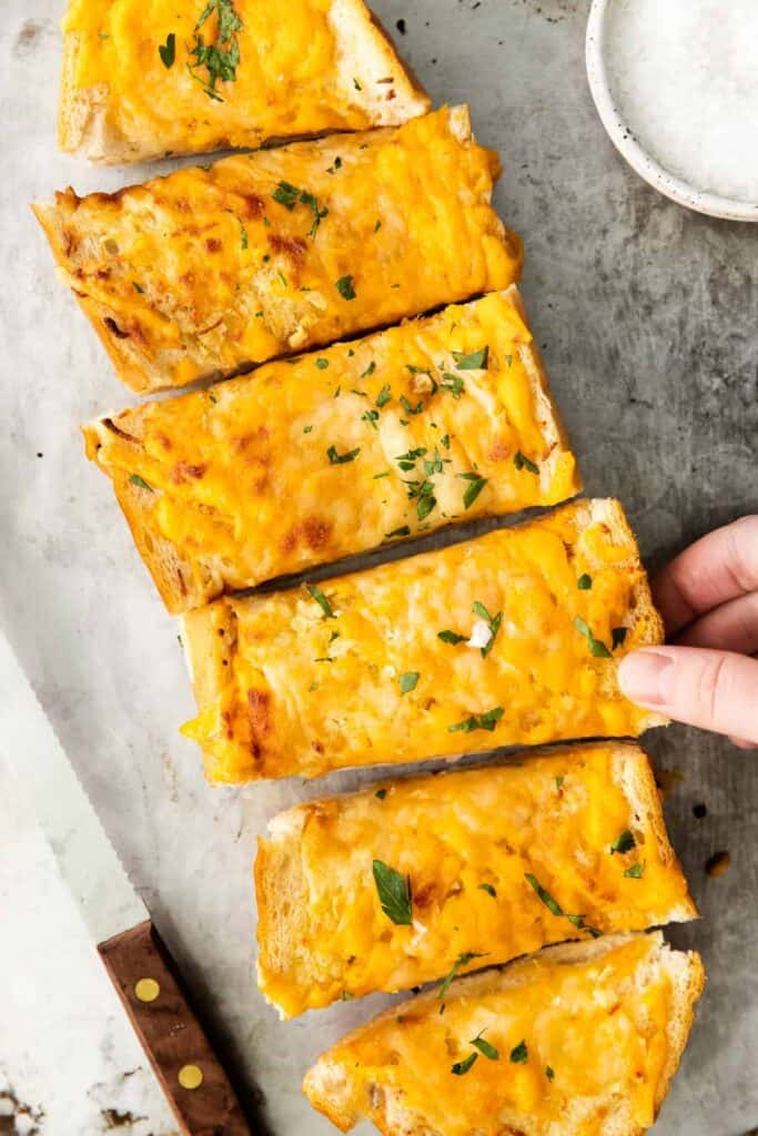 Garlic bread with chopped parsley on top.