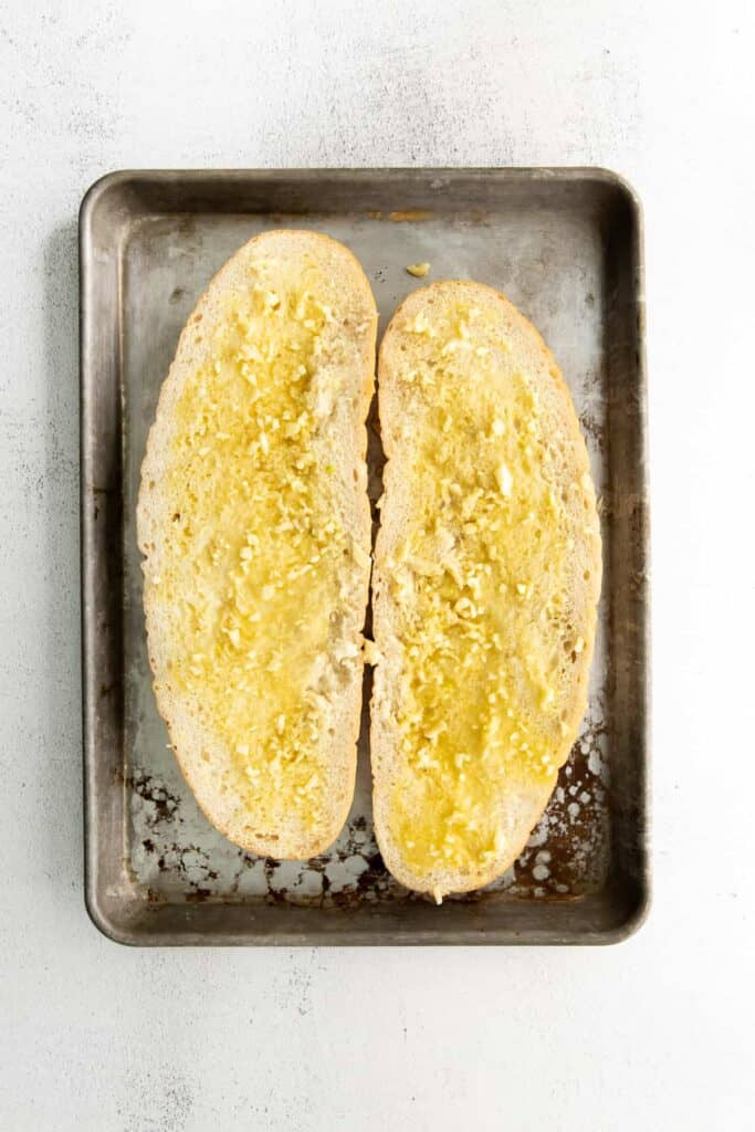 A loaf of bread with butter and garlic.