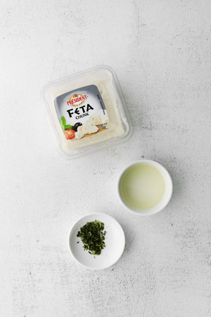 A bloc of feta, olive oil, and fresh thyme on a counter top.