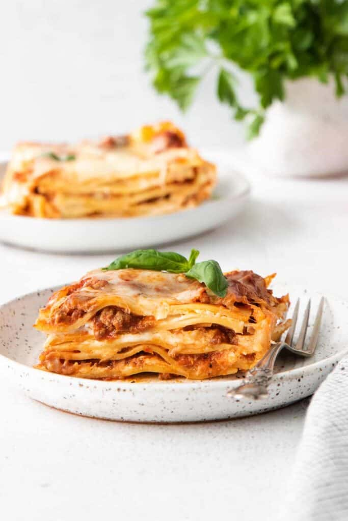 A piece of meat lasagna on a plate.