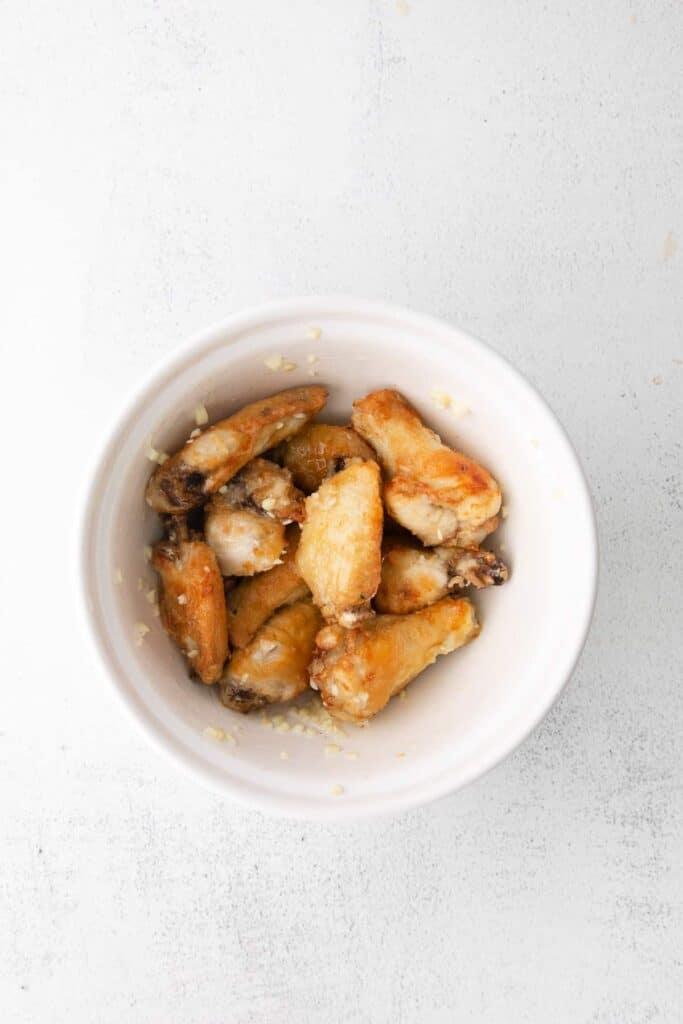 air fryer wings tossed in garlic parmesan sauce in a bowl