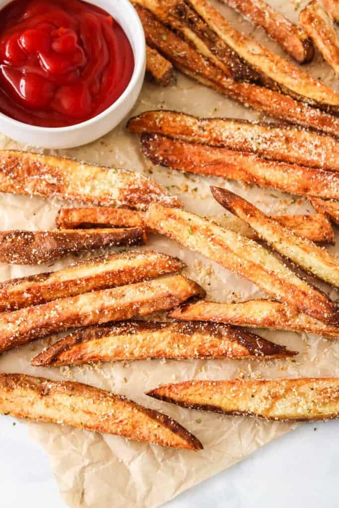 garlic parmesan fries on paper with ketchup