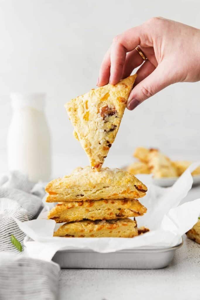 A hand holding a bacon and cheddar scone.