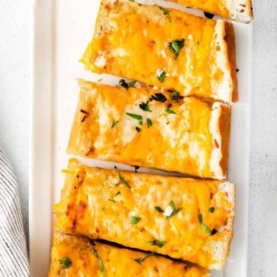 Cheesy garlic bread on a plate.