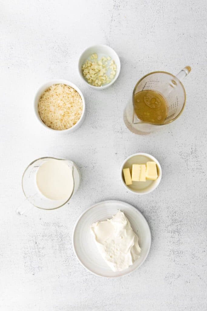 ingredients for alfredo sauce with cream cheese in small bowls