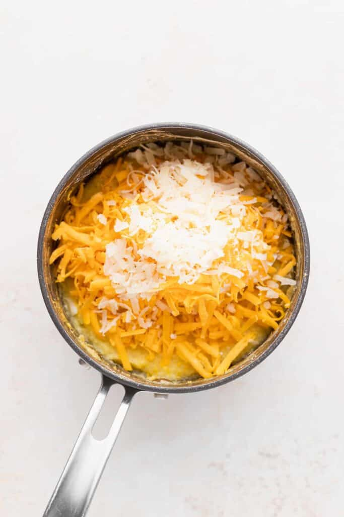 shredded parmesan cheese and yellow cheddar cheese in a pot with grits