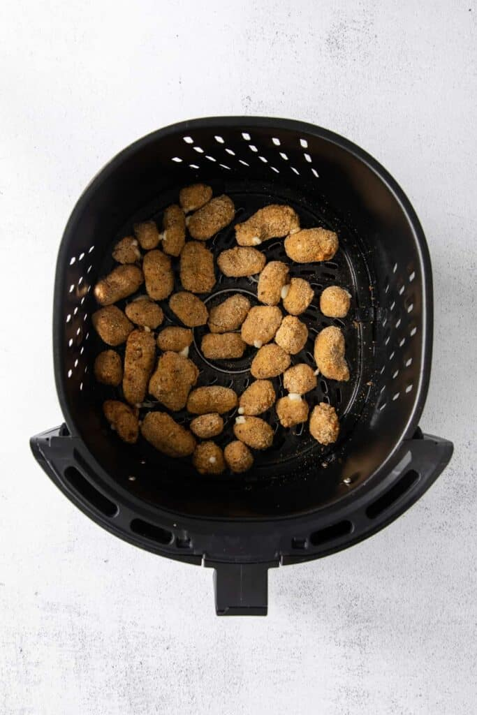cheese curds in an air fryer basket after being air fried
