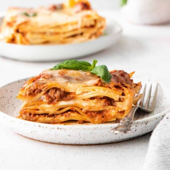 Meat lasagna on a plate with fresh basil on top.