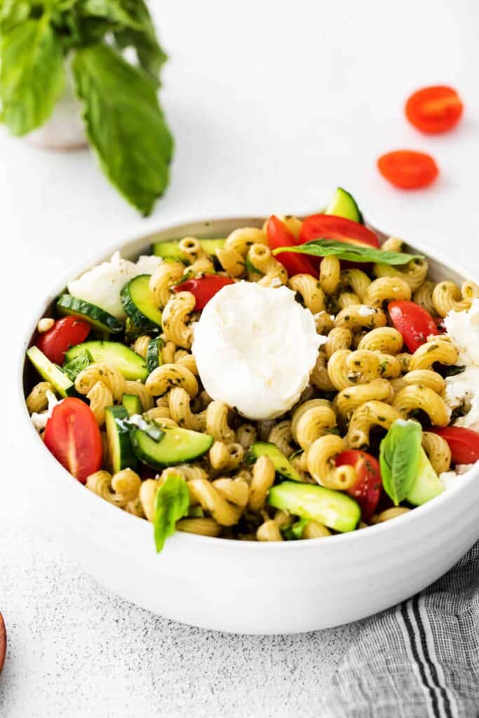 a ball of burrata pulled apart into chunks and placed over pesto pasta salad