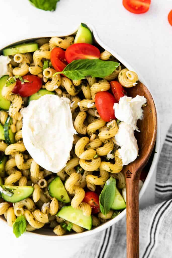 pesto pasta salad with burrata in a bowl with a wooden spoon ready to serve a delicious scoop