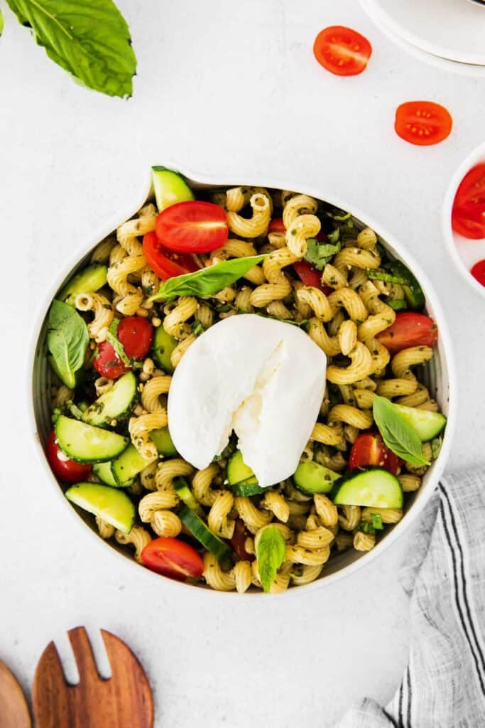 pesto pasta salad topped with burrata in a bowl, ready to be served