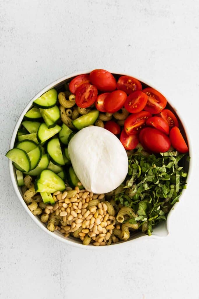 pesto pasta salad ingredients in a bowl and topped with a ball of burrata