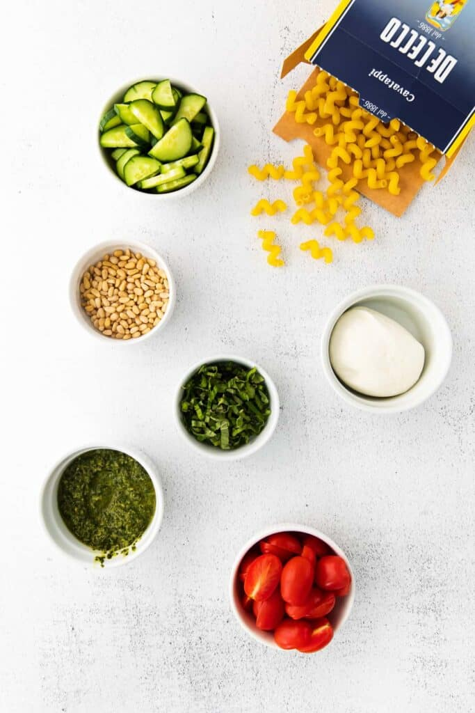 pesto pasta salad ingredients in bowls, ready to be tossed together