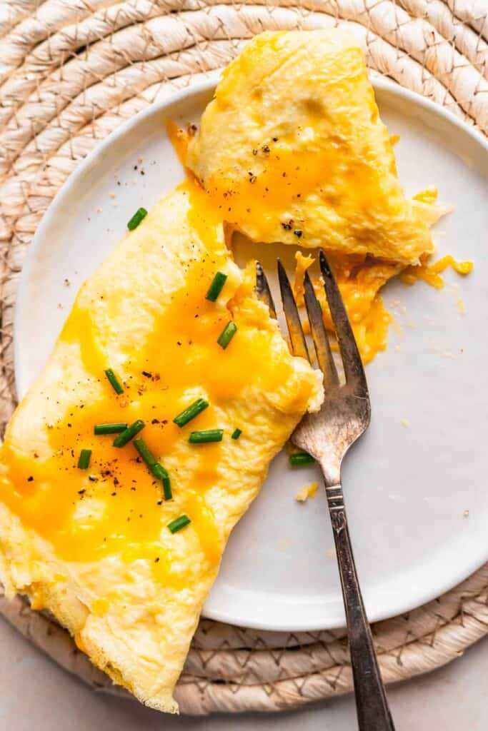 cheese omelette on a plate being cut open by a fork