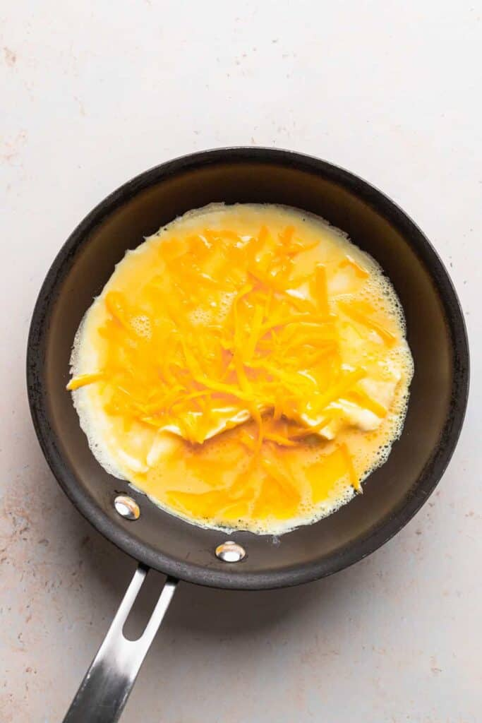 cheese omelette topped with shredded cheddar cheese in a skillet