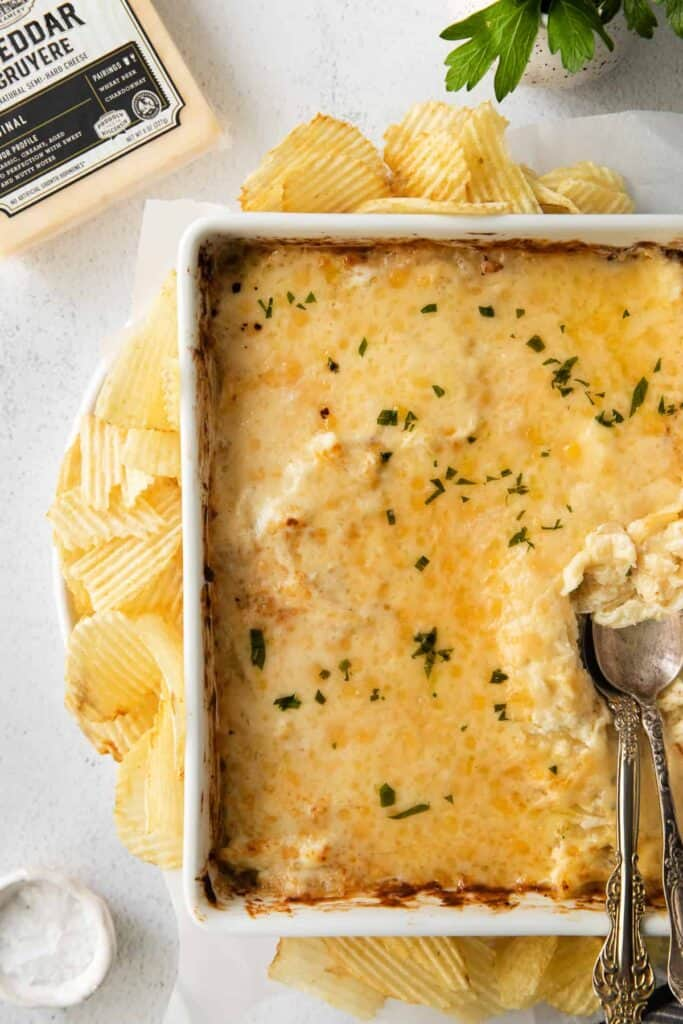 french onion dip in a casserole dish topped with fresh parsley