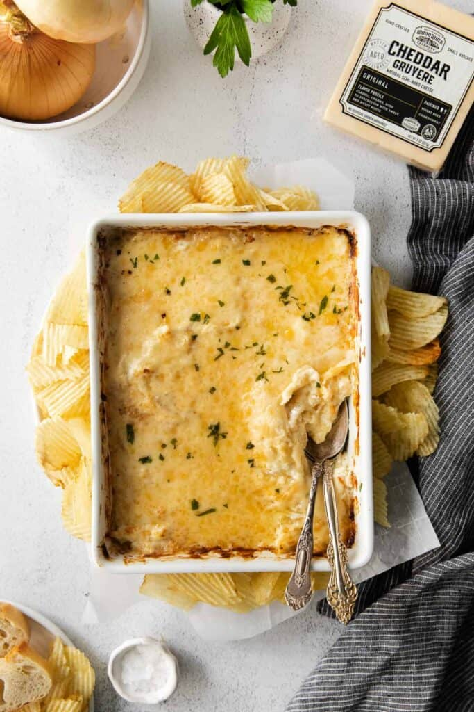 french onion dip in a casserole dish surrounded by potato chips